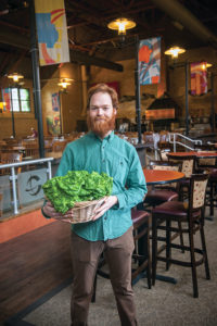Nick Pagan '15, pictured in the Clark cafeteria, holds a basket of lettuce he harvested from the university's Freight Farm.