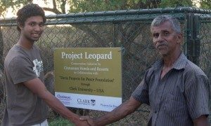 Sanjiv Fernando '15 (left) shakes hands with W.P. Piyadasa, a cattle herder who received one of Fernando's leopard-proof mesh enclosures.