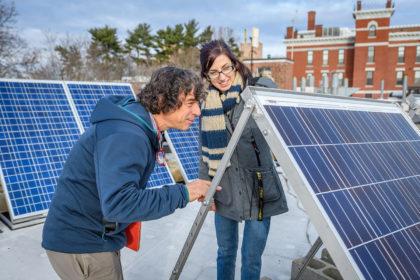 Chuck Agosta and Megan McIntyre looking at solar panels