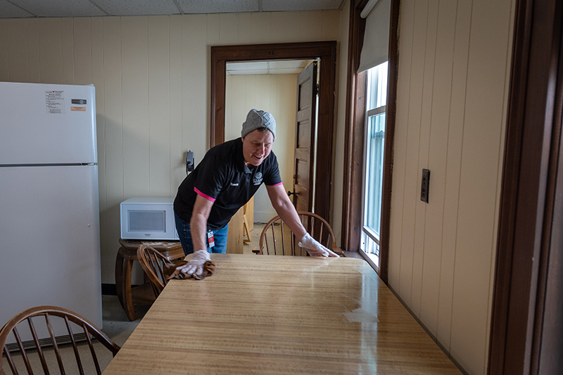 Facilities worker sanitizes student housing
