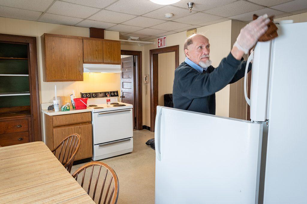 Bill Racki of Clark University Facilities Management cleans a student apartment