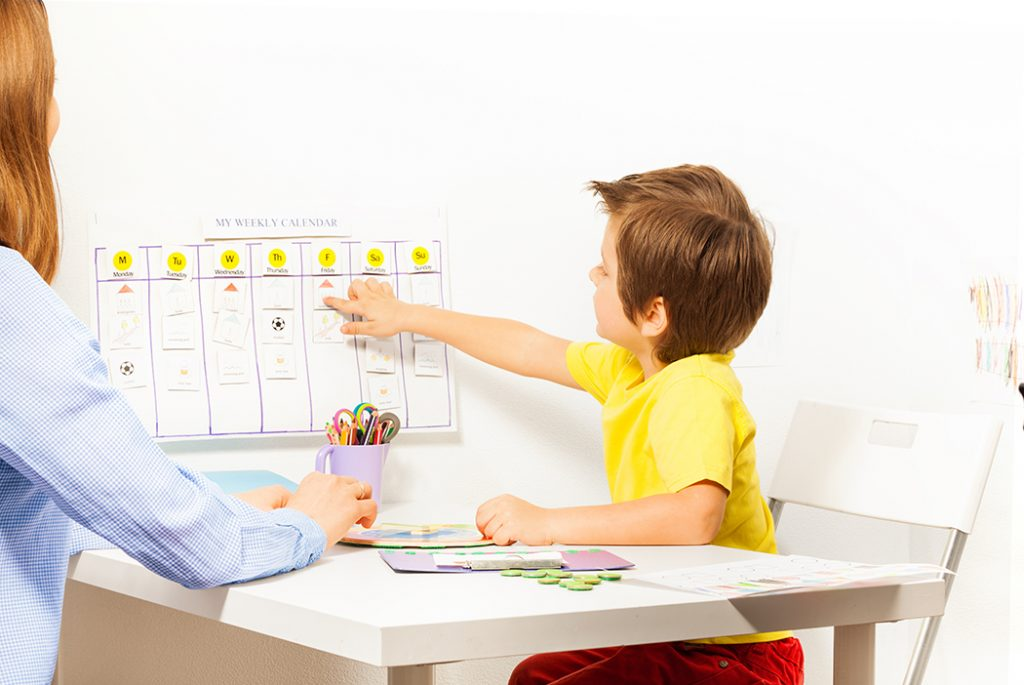 Boy pointing at schedule on a wall