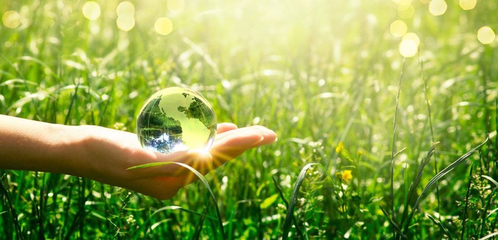 Earth Day - crystal glass globe in human hand on grass background. Saving environment and clean green planet concept. Card for World Earth Day concept.